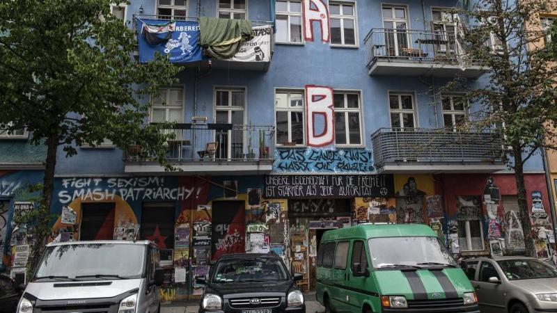 Fahrzeuge stehen an der Rigaer Straße vor dem Haus Nr. 94. Foto: Paul Zinken/dpa/Archivbild