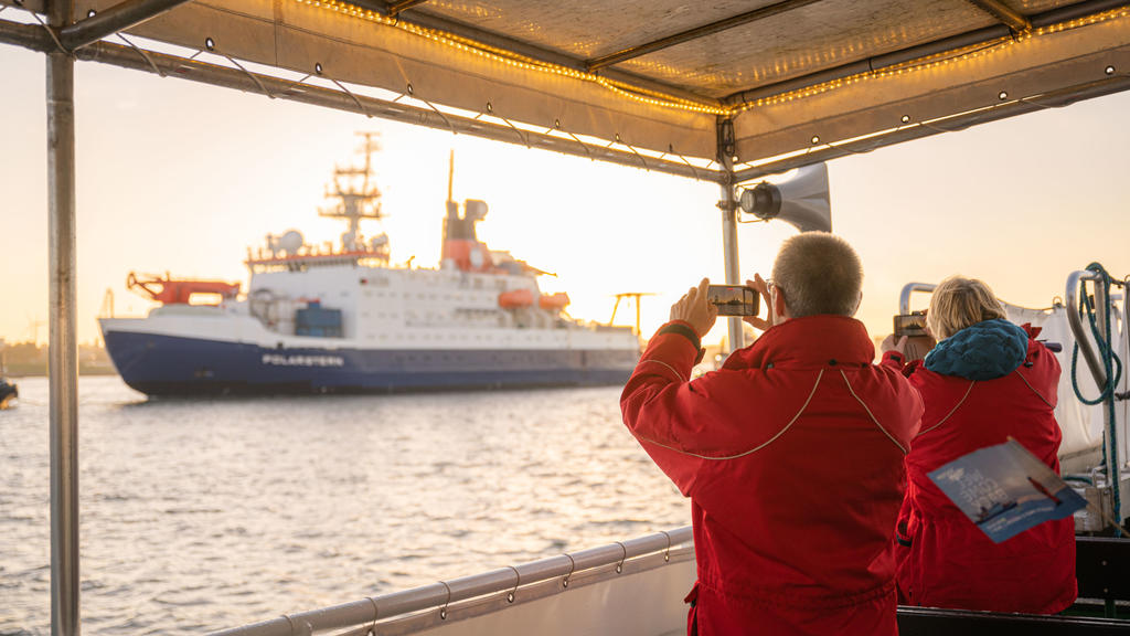 12.10.2020, Bremen, Bremerhaven: Zwei Personen auf einem Schiff fotografieren die Rückkehr des Forschungsschiffs ·Polarstern·. Foto: Mohssen Assanimoghaddam/dpa +++ dpa-Bildfunk +++