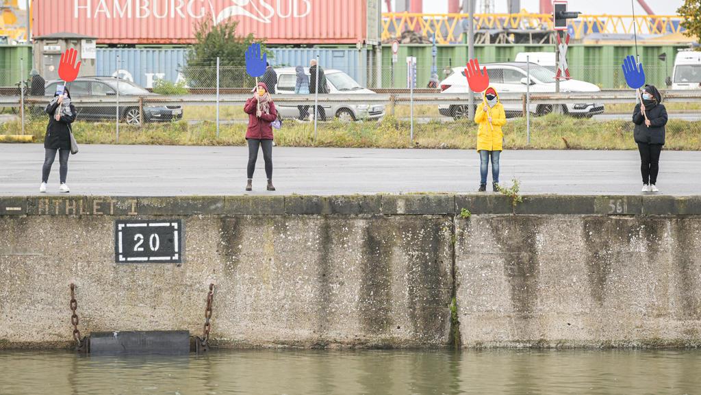 12.10.2020, Bremen, Bremerhaven: Vier Personen an einer Kaimauer winken während der Rückkehr des Forschungsschiffs ·Polarstern· mit blauen und roten Winkhänden. Foto: Mohssen Assanimoghaddam/dpa +++ dpa-Bildfunk +++
