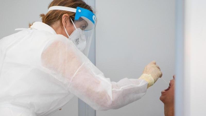 Eine Person wird auf das Coronavirus getestet. Foto: Christoph Schmidt/dpa/Archivbild