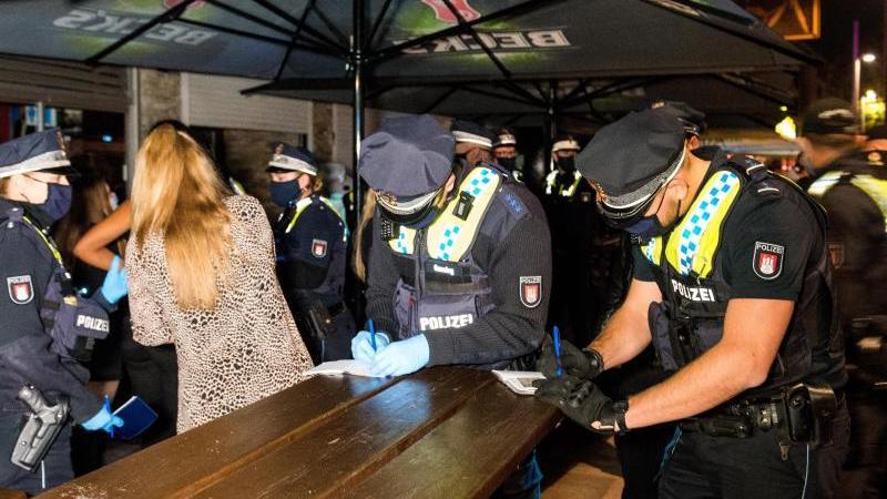 Polizisten nehmen vor einer Discothek auf der Reeperbahn die Personalien von Besuchern auf, die sich trotz der Sperrstunde verbotenerweise in dem Club aufgehalten und später versteckt haben. Foto: Daniel Bockwoldt/dpa/Aktuell