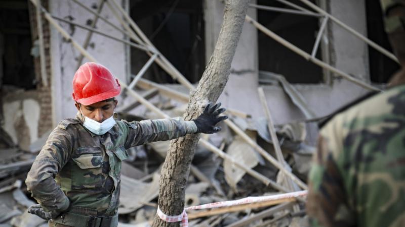 Ein aserbaidschanischer Soldat steht in der Nähe eines zerstörten Hauses in einem Wohngebiet, das von armenischen Streitkräften durch Raketenbeschuss getroffen wurde. Foto: Aziz Karimov/AP/dpa