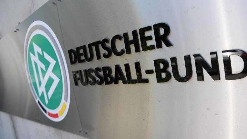 DFB-Logo und Schriftzug sind auf einer Palette angebracht. Foto: Arne Dedert/dpa/Symbolbild