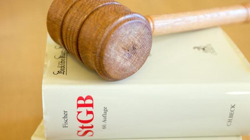 Ein Richterhammer und ein Strafgesetzbuch liegen auf einem Tisch. Foto: picture alliance / dpa