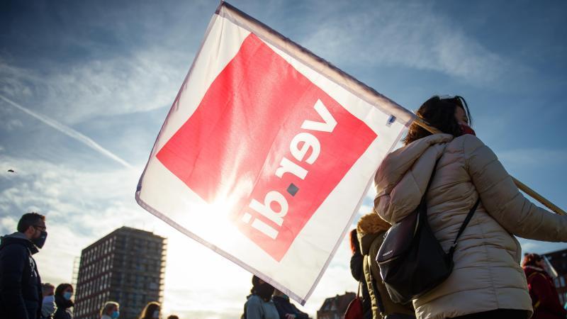 Menschen halten eine Verdi-Fahne. Foto: Gregor Fischer/dpa/Archivbild