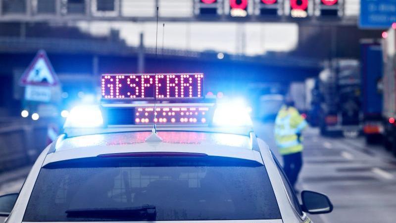 """Auf einem Polizeifahrzeug leuchtet die Aufschrift """"Gesperrt"""". Foto: David Young/dpa/Symbolbild"""