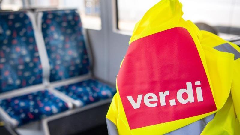 """Eine Warnweste mit der Aufschrift """"ver.di"""" liegt in einer leeren Straßenbahn. Foto: Sina Schuldt/dpa/Archivbild"""