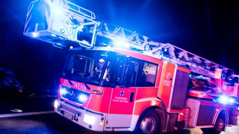 Ein Drehleiterwagen der Feuerwehr ist mit Blaulicht imEinsatz. Foto: Marcel Kusch/dpa/Illustration
