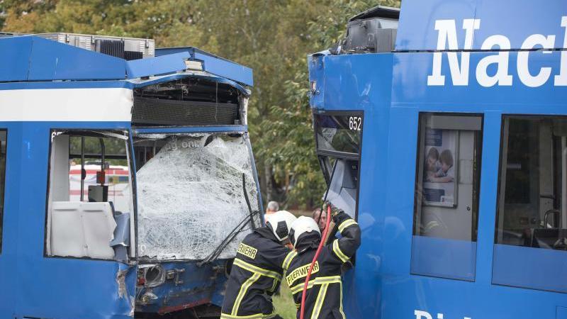 Feuerwehrleute arbeiten nach einer Straßenbahnkollision am Unfallort. Foto: Frank Hormann/dpa