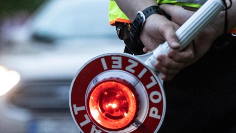 Ein Polizist hält eine Winkerkelle in der Hand. Foto: Paul Zinken/dpa/ZB/Symbolbild