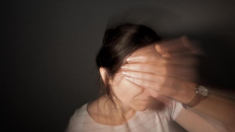 Eine Frau fasst sich an den Kopf. Foto: Oliver Killig/dpa-Zentralbild/dpa/Archivbild
