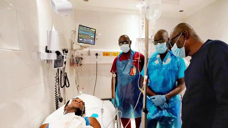 Babajide Sanwo-Olu (r.), Gouverneur des Bundesstaats Lagos, besucht einen Mann, der bei Protesten verletzt wurde, im Krankenhaus. Foto: -/Lagos State government press/AP/dpa
