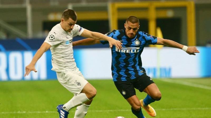 Stefan Lainer von Borussia Mönchengladbach und Alexis Sanchez von Inter Mailand (l-r.) in Aktion. Foto: Cezaro de Luca/dpa
