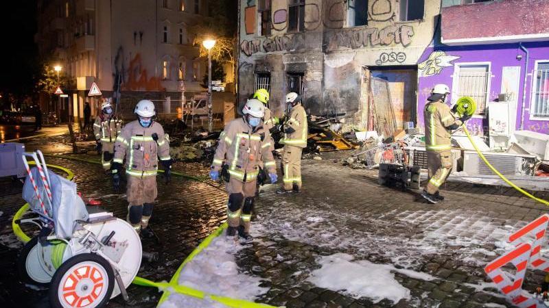 """Feuerwehrkräfte sind vor dem geräumten Hausprojekt """"Liebig 34"""" im Einsatz. Foto: Christoph Soeder/dpa"""