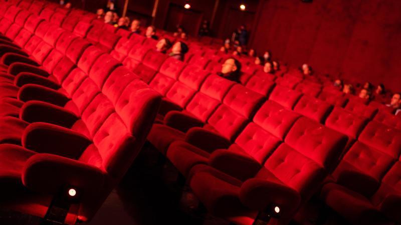 Kinobesucher sitzen in großen Abständen im Kinosaal. Foto: Nicolas Armer/dpa/Archivbild