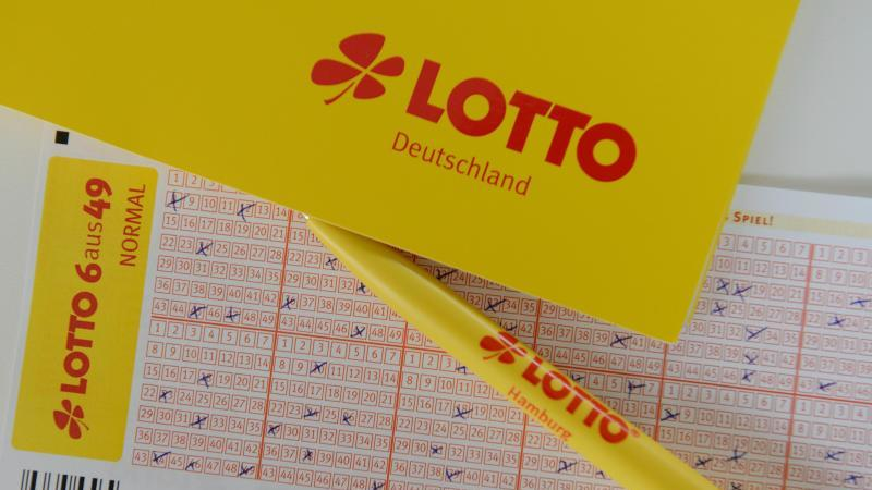 Lottoscheine liegen auf einem Tisch. Foto: picture alliance / Daniel Reinhardt/dpa/Symbol