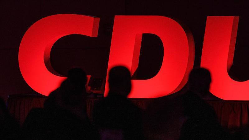 CDU-Delegierte sitzen vor dem Partei-Logo. Foto: Swen Pförtner/dpa/Symbolbild