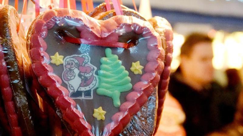Ein Lebkuchenherz hängt an einem Stand auf einem Weihnachtsmarkt. Foto: David Schwarz/dpa/Archivbild
