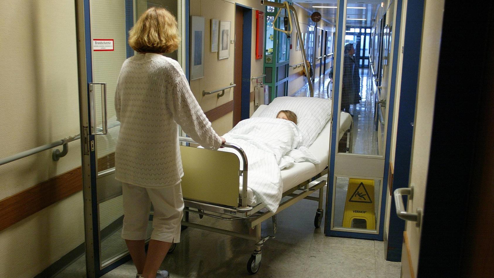 Thema Gesundheitspolitik Krankenhaus Krankenschwester schiebt eine Patientin im Bett Berlin