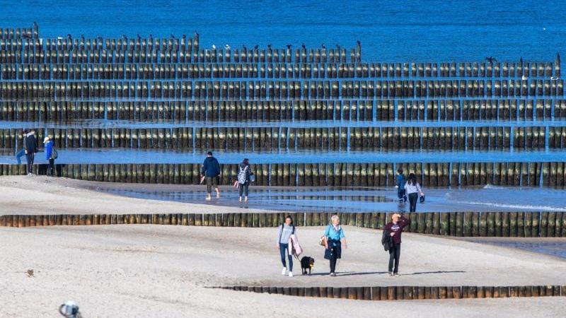 Spaziergänger am Strand von Koserow auf der Ostseeinsel Usedom. Foto: Jens Büttner/dpa-Zentralbild/dpa