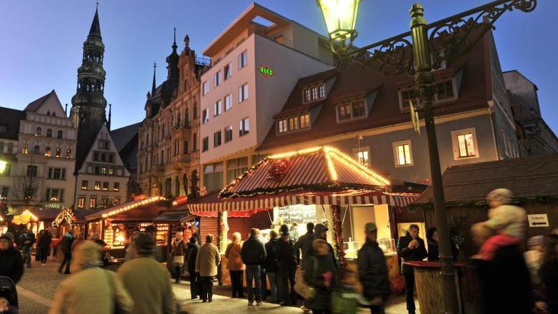 Besucher der Zwickauer Innenstadt gehen über den Weihnachtsmarkt der Stadt. Foto: Hendrik Schmidt/dpa-Zentralbild/dpa