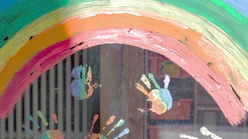 Kinderhände und ein Regenbogen sind an einer Kita zu sehen. Foto: Jens Kalaene/dpa-Zentralbild/dpa/Symbolbild