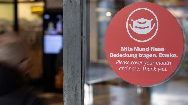Ein Schild an einer Tür weist auf das Tragen eines Mund-Nasen-Schutzes hin. Foto: Paul Zinken, Christoph Soeder/dpa