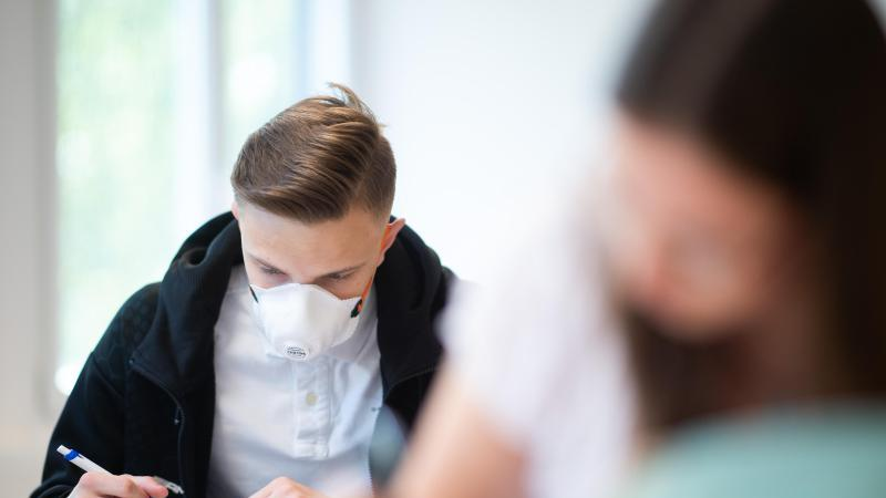 Schülerinnen und Schüler, einer davon mit einer Schutzmaske, bearbeiten Aufgaben. Foto: Jonas Güttler/dpa/Archivbild