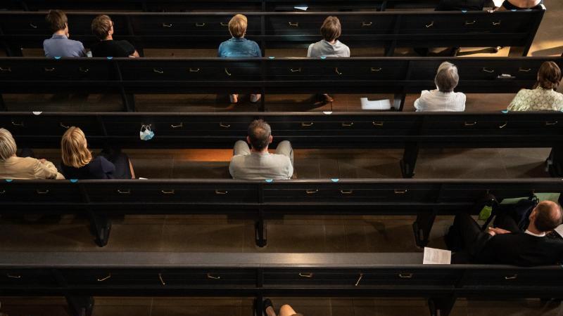 Teilnehmer sehen sich in einer Kirche eine Konfirmation an. Foto: Christoph Schmidt/dpa/Archivbild