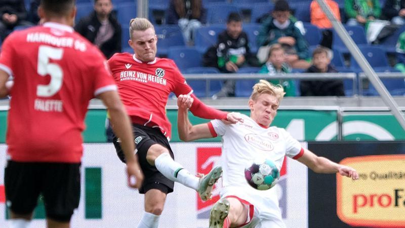 Hannovers Niklas Hult (l) und Düsseldorfs Christoph Klarer kämpfen um den Ball. Foto: Peter Steffen/dpa