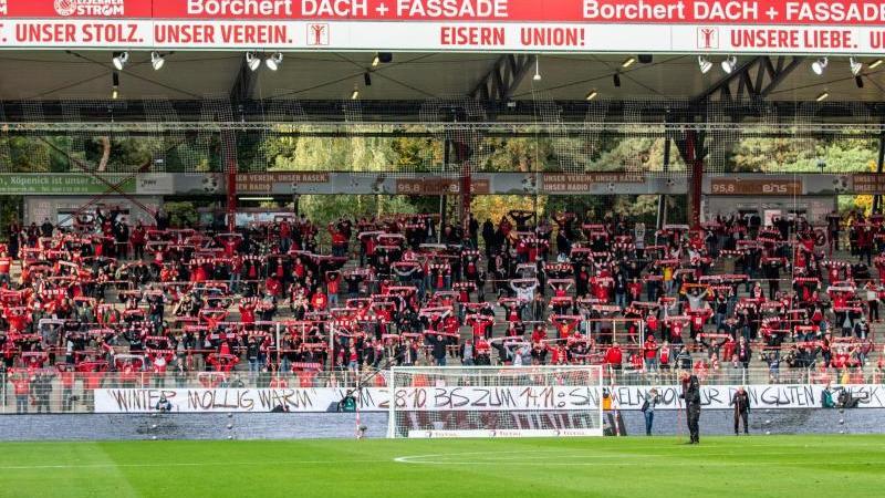Fans von Union Berlin feuern ihr Team mit Schals an. Foto: Andreas Gora/dpa-Pool/dpa