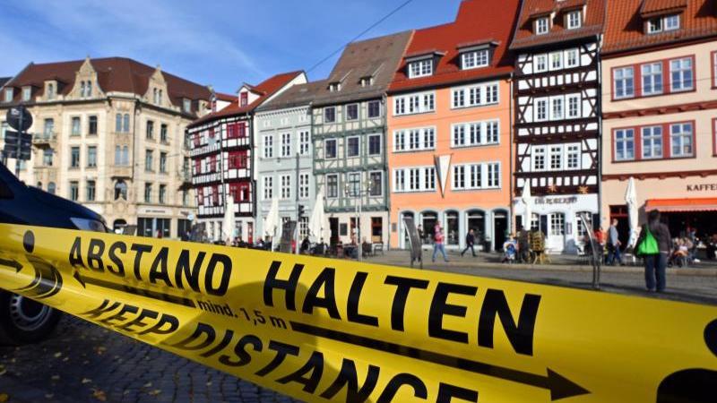 """""""Abstand halten!"""" in deutscher und englischer Sprache steht auf einem Flatterband am Domplatz. Foto: Martin Schutt/dpa-Zentralbild/dpa/Archivbild"""