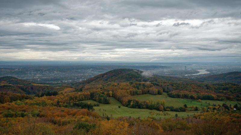 Schwere Wolken schweben über den herbstlichen Wäldern des Siebengebirges. Foto: Henning Kaiser/dpa/Archivbild