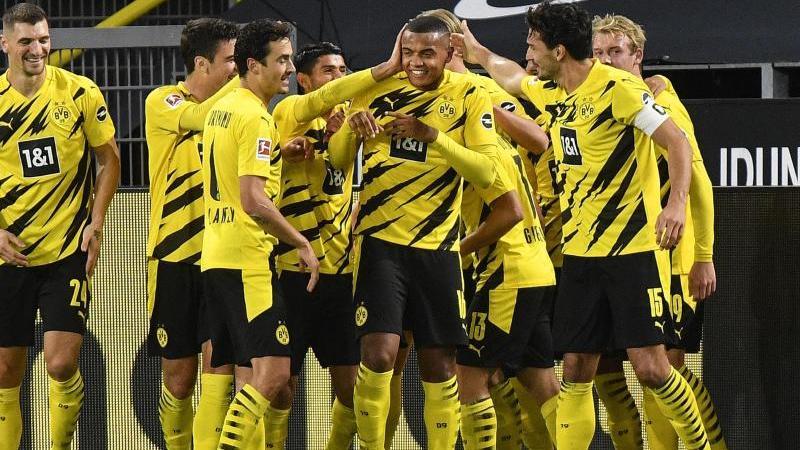 Der Dortmunder Manuel Akanji (M) wird gefeiert, nachdem er das das Eröffnungstor im Revier-Derby erzielt hat. Foto: Martin Meissner/AP-Pool/dpa