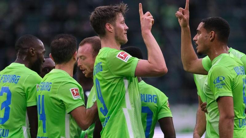 Wolfsburgs Wout Weghorst (M) bejubelt sein Tor zum 1:0 gegen Arminia Bielefeld mit Mannschaftskamerad Maxence Lacroix (r). Foto: Peter Steffen/dpa