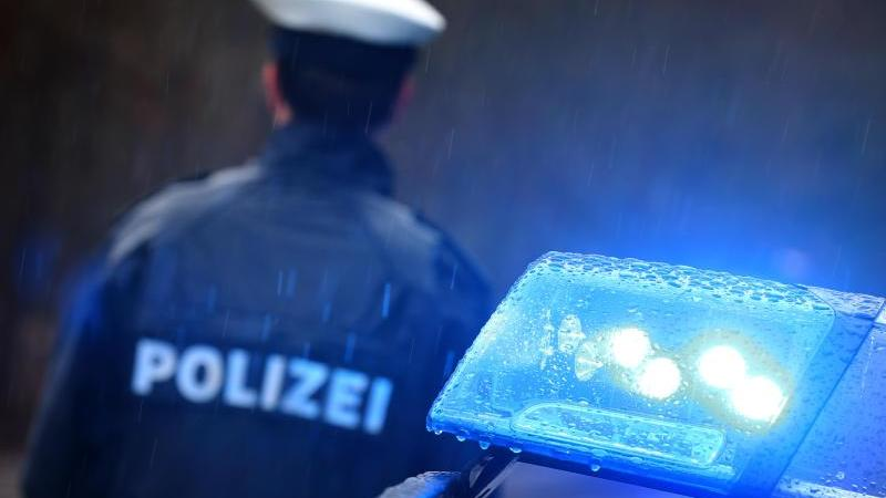 Ein Polizist steht im Regen vor einem Streifenwagen dessen Blaulicht aktiviert ist. Foto: Karl-Josef Hildenbrand/dpa/Archivbild