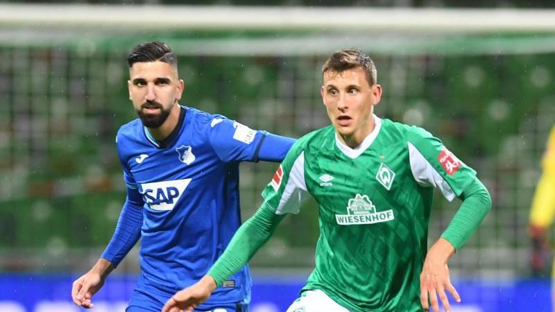 Werders Maximilian Eggestein (r) kämpft gegen Hoffenheims Munas Dabbur um den Ball. Foto: Carmen Jaspersen/dpa