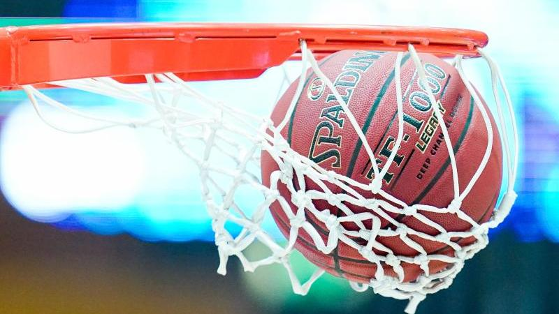 Ein Basketball landet im Korb. Foto: Uwe Anspach/dpa/Symbolbild