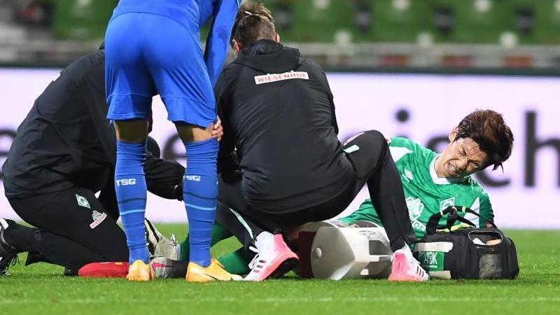 Werders Yuya Osako liegt am Boden und wird von Ärzten behandelt. Foto: Carmen Jaspersen/dpa