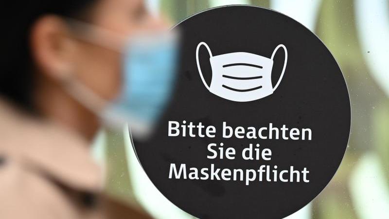 Eine Frau mit Mundschutz geht an einem Schaufenster vorbei, dass auf die Maskenpflicht hinweist. Foto: Arne Dedert/dpa/Symbolbild