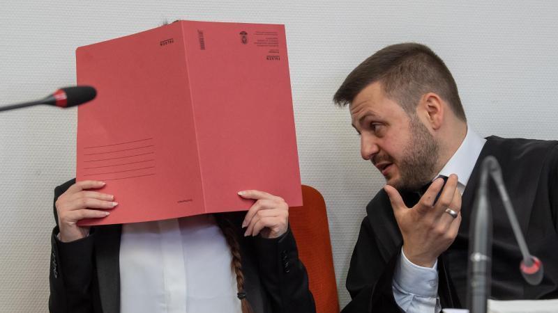 Die Angeklagte hält einen roten Aktendeckel vor ihr Gesicht. Foto: Peter Kneffel/dpa/Archivbild