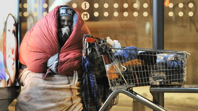 In Schlafsack und Decken gehüllt sitzt eine obdachlose Frau an einer Bushaltestelle. Foto: picture alliance/dpa/Symbolbild