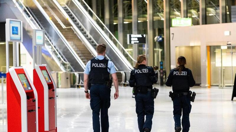 Drei Polizisten gehen durch das Terminal 1 am Flughafen. Foto: Andreas Arnold/dpa/Archivbild