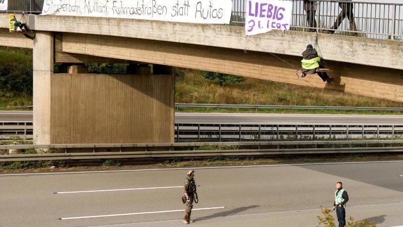 Umweltaktivisten hängen an einer Brücke über der Autobahn 3 und protestieren gegen die Rodung von Bäumen im Herrenwald und Dannenröder Forst bei Stadtallendorf im Zusammenhang mit dem geplanten Ausbau der Autobahn 49. Foto: Jörg Halisch/dpa/Archivbild