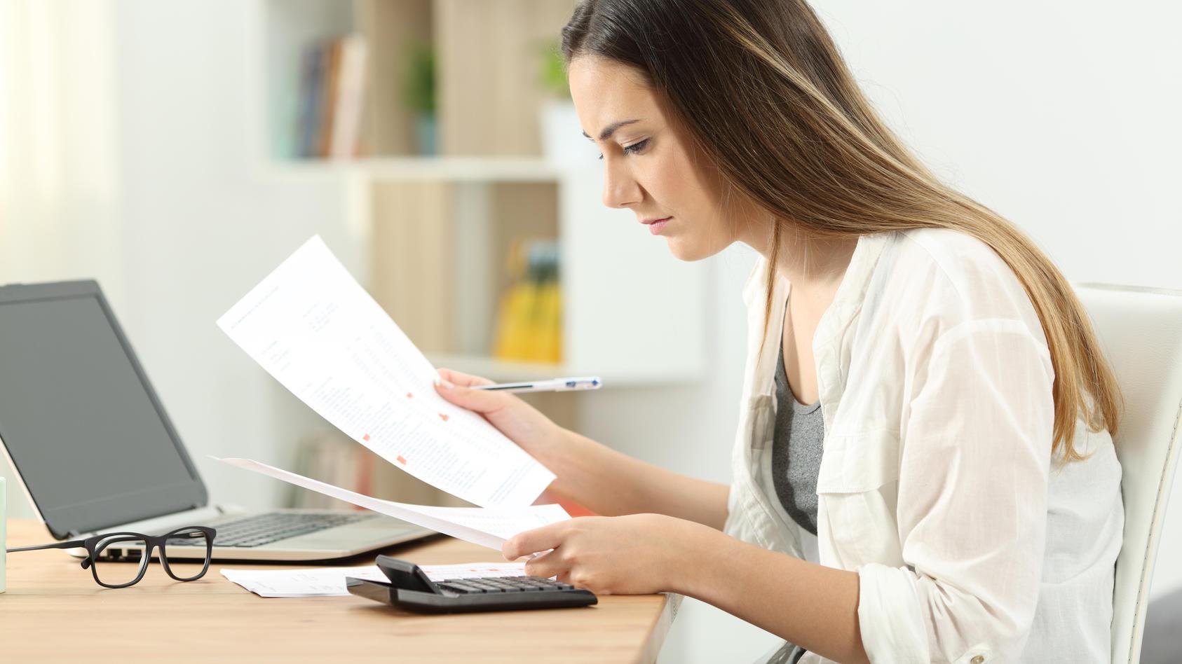 Frau überprüft ihre Gehaltsabrechnung.