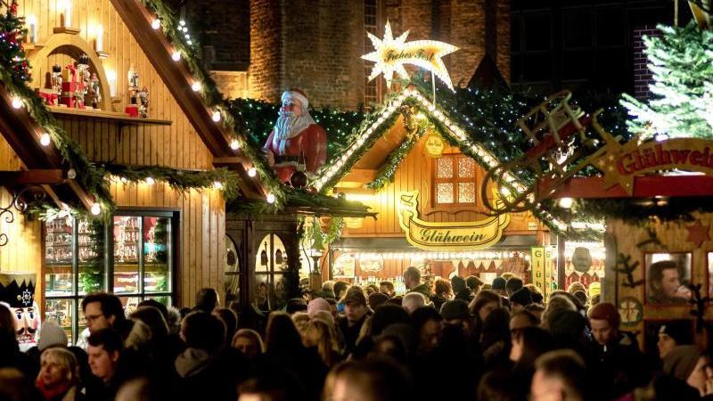 Besucher gehen über den Weihnachtsmarkt nahe der Marktkirche in Hannover. Foto: Hauke-Christian Dittrich/dpa/Archivbild