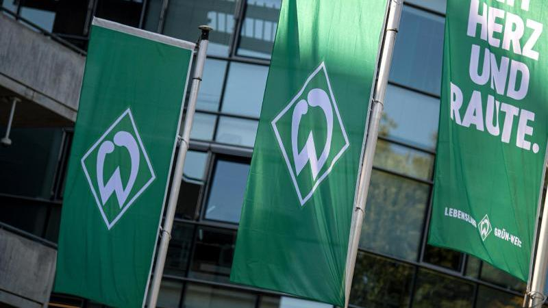 Flaggen mit dem Logo des Werder Bremen wehen im Wind. Foto: Sina Schuldt/dpa/Archivbild
