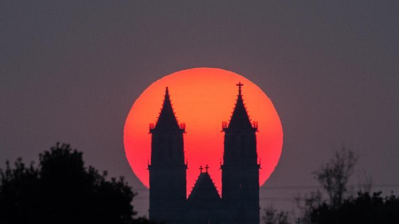 Die Abendsonne geht hinter dem Magdeburger Dom unter. Foto: Lukas Schulze/dpa/Archivbild