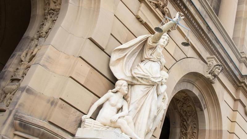 Vor dem Gerichtsgebäude hält eine Statue der Justitia eine Waagschale. Foto: Stefan Puchner/dpa/Archivbild