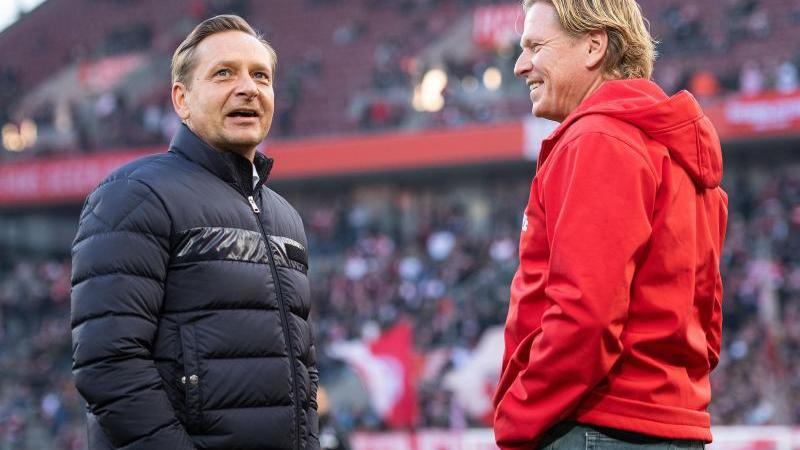 Horst Heldt (l) und Markus Gisdol unterhalten sich vor einer Partie. Foto: Marius Becker/dpa/Archivbild